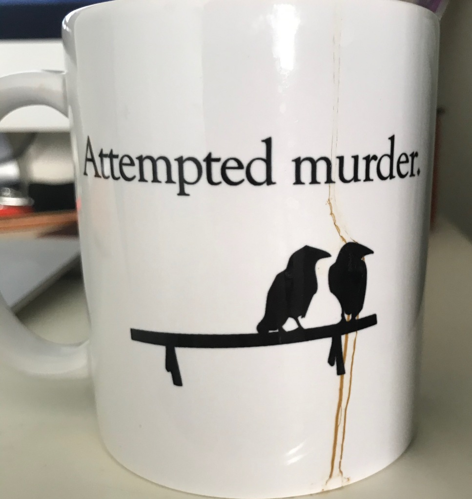 "A coffee mug that says ""Attempted murder."" Pictured below the words are two crows on a bench. A coffee stain runs from the top of the mug through one of the crows to the bottom."
